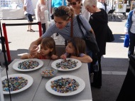 Chloe Waterfield and her dauther Lucaya, left, and friend Jillian Jennings at Kathy French lampwork booth. Photo credit: Ken Kaminsky